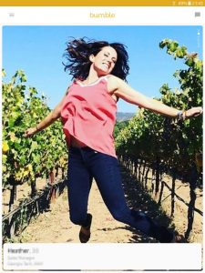 Example of a Bumble profile picture: girl jumping among grapevines
