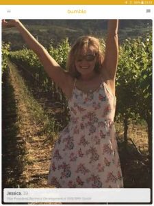Example of a Bumble profile picture: woman posing at a vineyard